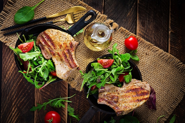 Juicy grilled pork steak with herbs on bone on wooden surface