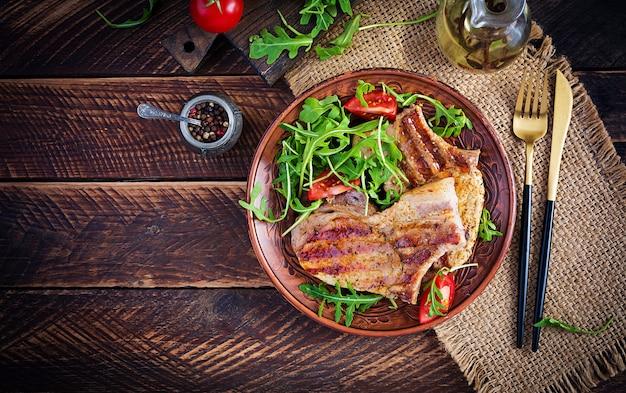 Сочный стейк из свинины на гриле с зеленью на кости на деревянной поверхности