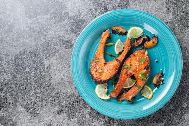 돌 슬레이트 테이블에 파란색 청록색 생선 접시에 레몬, 향신료, 라임과 맛있게 구운 연어 스테이크. 맛있게 조리 된 연어 필레