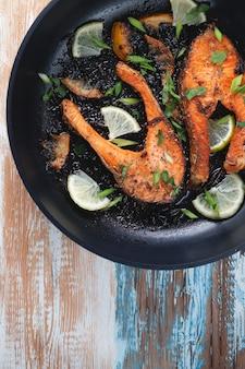 가벼운 나무 테이블에 프라이팬에 레몬, 향신료, 라임과 맛있게 구운 연어 스테이크. 맛있게 조리 된 연어 필레