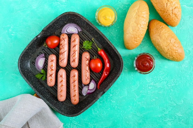 Juicy grilled sausages on grill pan with vegetables and crispy bun. top view. ingredients for hot dogs. flat lay.