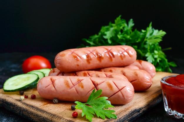 Сочные колбаски гриль, соус и свежие овощи. колбаски для хот-дога. уличная забегаловка.