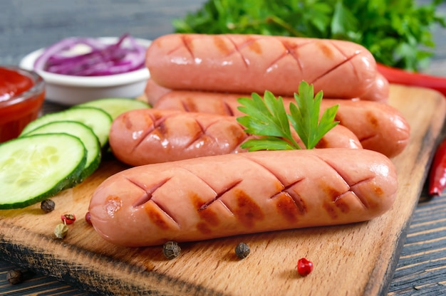 Juicy grilled sausages, sauce and fresh vegetables. sausages for hot dog. street food.