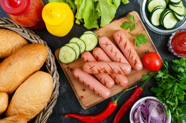 Сочные жареные колбаски, соусы, свежие овощи, хрустящие булочки, на деревянном фоне. вид сверху. flatlay. ингредиенты для хот-дога. уличная забегаловка.