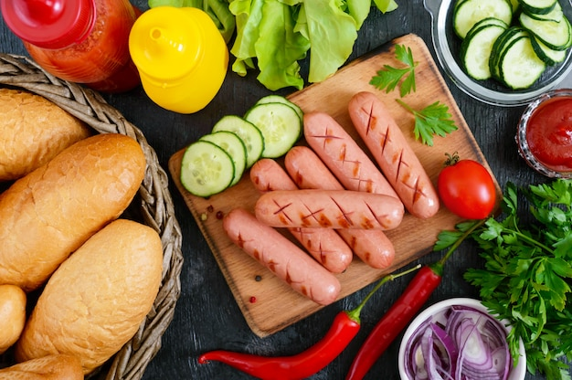 Juicy grilled sausages, sauces, fresh vegetables, crispy buns, on a wooden background. top view. flatlay. ingredients for a hot dog. street food.