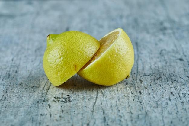 Juicy half cut yellow lemon on marble surface