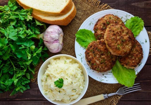 Сочные домашние котлеты (говядина, свинина, курица) и картофельное пюре на деревянном фоне. вид сверху.