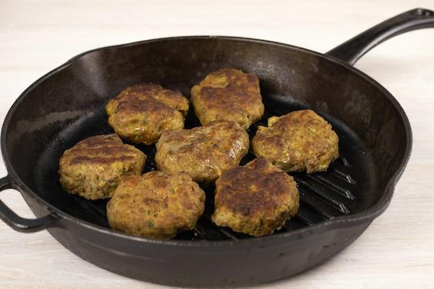 ジューシーな自家製ミートバーガーパテカツレツビーフ、ポーク、チキン、ターキーを白いテーブルに黒い鋳鉄のフライパンで。ケトジェニック、肉食動物、低炭水化物ダイエットのコンセプト。