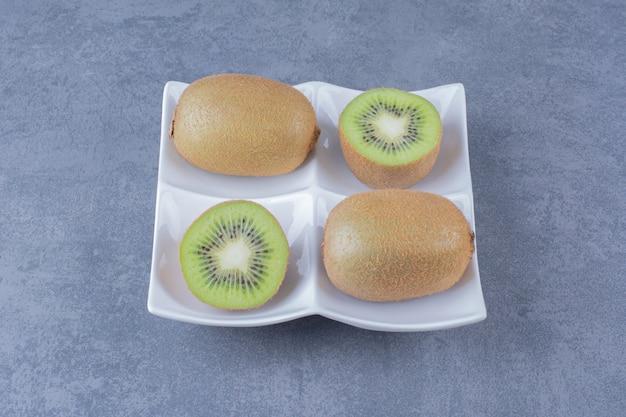 Kiwi succosi in un tavolo di marmo plateon.