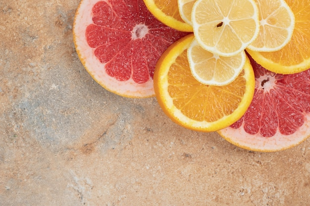 大理石の背景にジューシーなレモン、オレンジ、グレープフルーツのスライス。