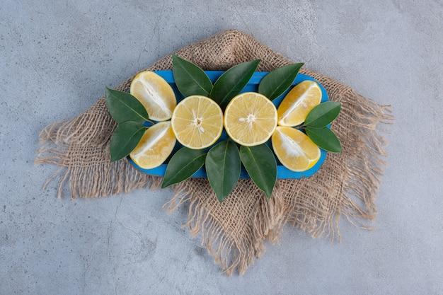 大理石の背景に青い大皿にジューシーなレモンスライスと葉。