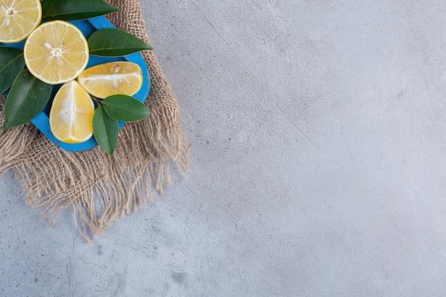 달콤한 레몬 조각과 대리석 바탕에 파란색 플래터에 나뭇잎.