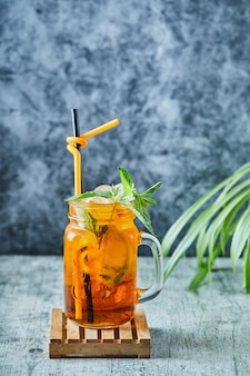 Сочный лимонад с соломой и мятой на поверхности растения