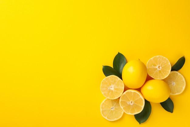 Сочные лимоны и листья на желтом фоне, вид сверху