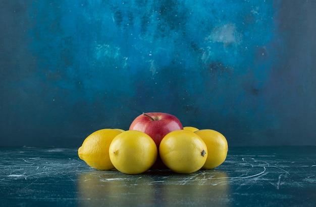 大理石のテーブルにジューシーなレモンと赤いリンゴ。