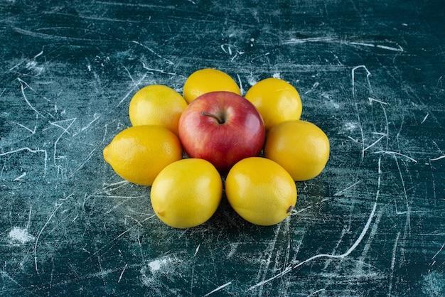 달콤한 레몬과 대리석 테이블에 빨간 사과.
