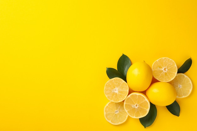 Juicy lemons and leaves on yellow background, top view