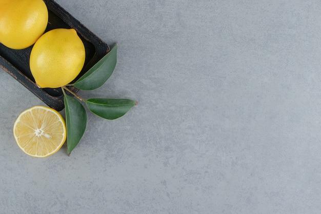 Limoni succosi su un piccolo vassoio ornato di foglie su marmo