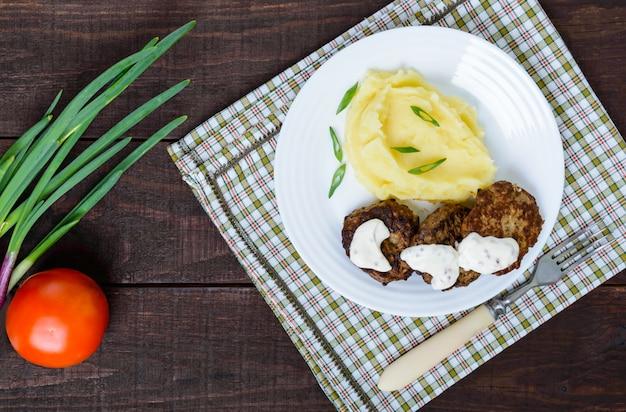 Сочная печеночная котлета с соусом и картофельным пюре на белой тарелке