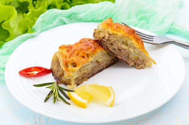 Сочная мясная котлета, запеченная с тертым картофелем и сыром на белой керамической тарелке. закрыть вверх
