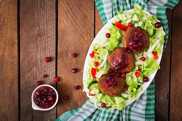 クランベリーソースと素朴なスタイルの木製テーブルのサラダとジューシーな肉カツレツ。上面図