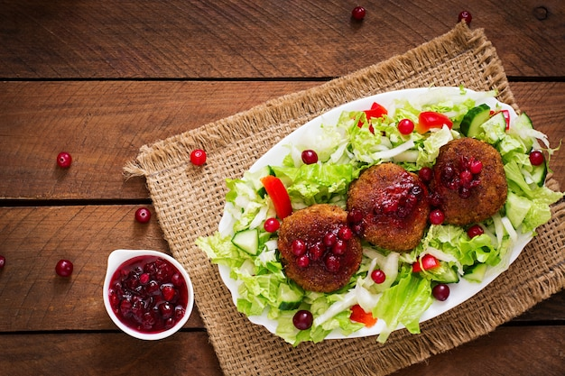 크랜베리 소스와 소박한 스타일의 나무 테이블에 샐러드와 육즙 고기 cutlets. 평면도