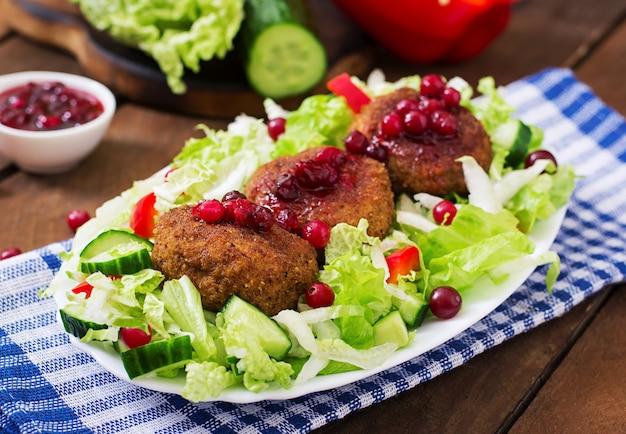 クランベリーソースと素朴なスタイルの木製テーブルのサラダとジューシーな肉カツレツ。
