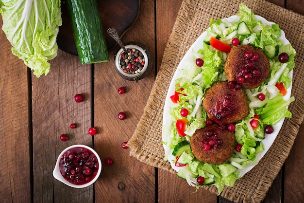 Juicy meat cutlets with cranberry sauce and salad on a wooden table in a rustic style. top view