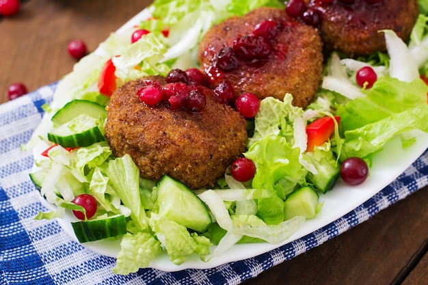 Juicy meat cutlets with cranberry sauce and salad on a wooden table in a rustic style.