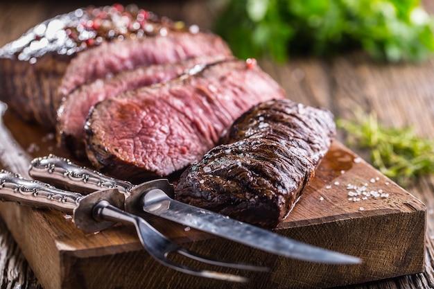 Сочные кусочки стейка rib eye из говядины среднего размера на деревянной доске с вилкой и ножом, зеленью, специями и солью
