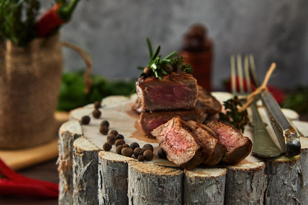 Juicy medium pieces of rib eye beef steak in a pan on a wooden board with a fork and knife
