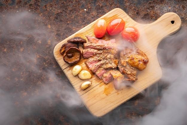 녹슨 질감 배경의 나무 커팅 보드에 토마토, 버섯, 마늘, 오레가노를 곁들인 육즙이 많은 희귀 구운 쇠고기 필레 스테이크 고기, 텍스트 복사 공간, 위쪽 전망