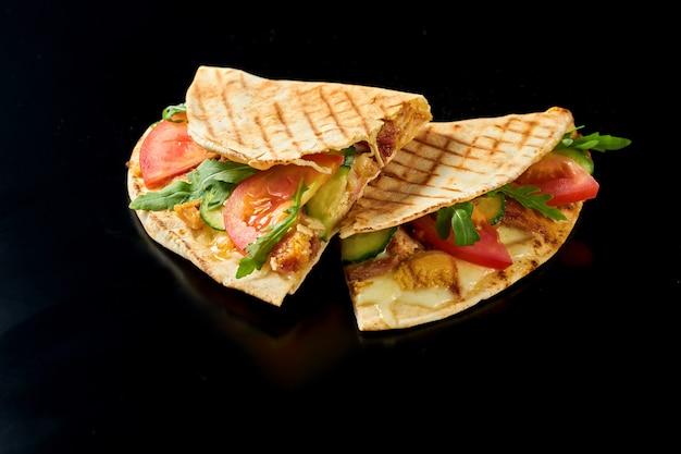 鶏肉、溶けたチーズ、トマト、きゅうり、ルッコラを添えたジューシーなメキシコのケサディーヤ。黒い表面で隔離。屋台の食べ物。クローズアップ、セレクティブフォーカス
