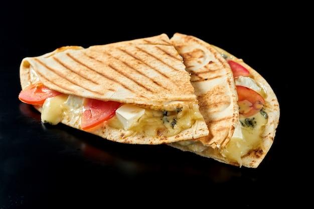 モッツァレラチーズ、カマンベールチーズ、ブルーチーズ、トマトを添えたジューシーなメキシコのケサディーヤ。黒い表面で隔離。屋台の食べ物。クローズアップ、セレクティブフォーカス