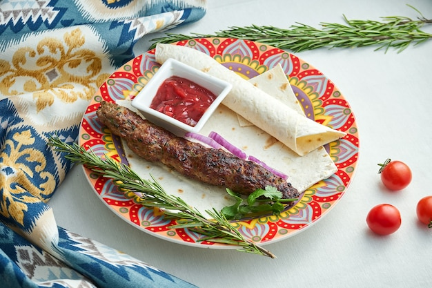 Juicy minced meat lula kebab in a patterned plate with red sauce and lavash on white plate