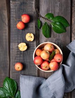 古い木製の背景にリネンタオルとボウルにジューシーなミニリンゴ。素朴なスタイルと上面図