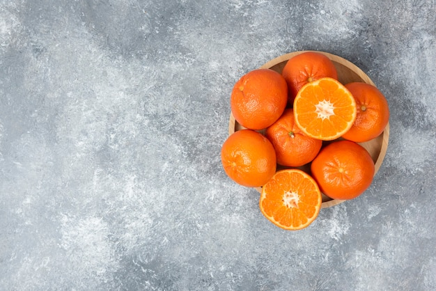石のテーブルの上の木の板のスライスとジューシーなオレンジ色の果物。