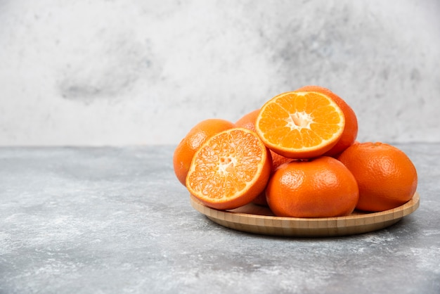 Juicy orange fruits with slices in a wooden plate on stone table .
