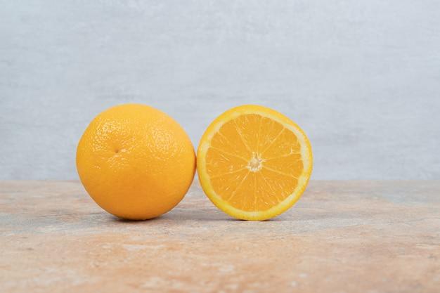 Arancia succosa e arancia tagliata a metà sul tavolo di marmo.