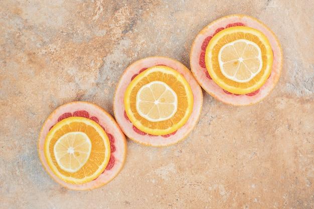 大理石の表面にジューシーなオレンジ、レモン、グレープフルーツのスライス。