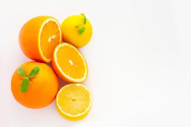 白い背景にジューシーオレンジ。オレンジスライスと白い背景で隔離の葉とオレンジ色の果物。ビタミンc.オレンジのクローズアップ。ベジタリアン、ビーガンフード。新鮮な柑橘系の果物。オレンジ色のレモン。