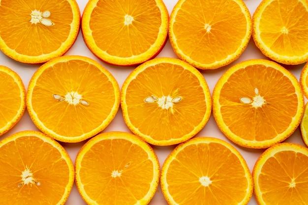 白い背景にジューシーオレンジオレンジスライスと白い背景で隔離の葉とオレンジ色の果物。ビタミンcオレンジのクローズアップ。ベジタリアン、ビーガン料理。シトラスフルーツ。健康な皮膚栄養