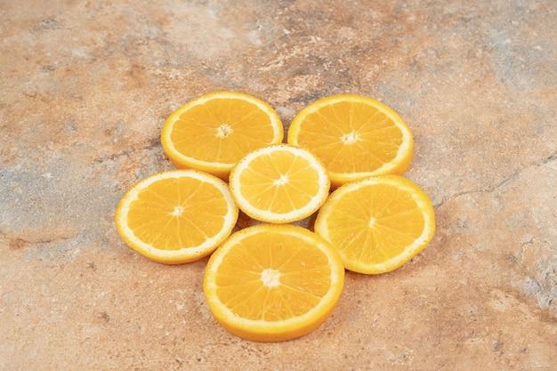 Сочные дольки апельсина на мраморной поверхности.