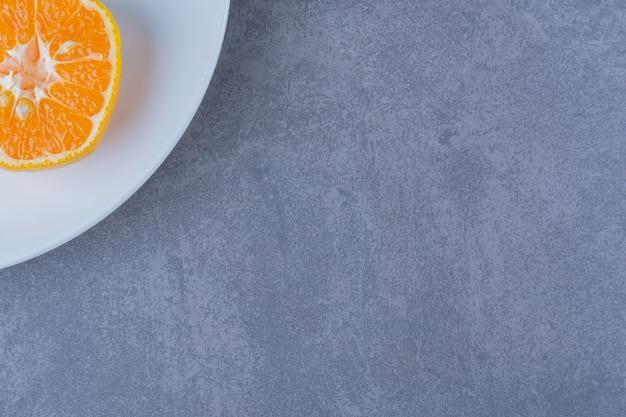 Сочные апельсины на тарелке на мраморном столе.