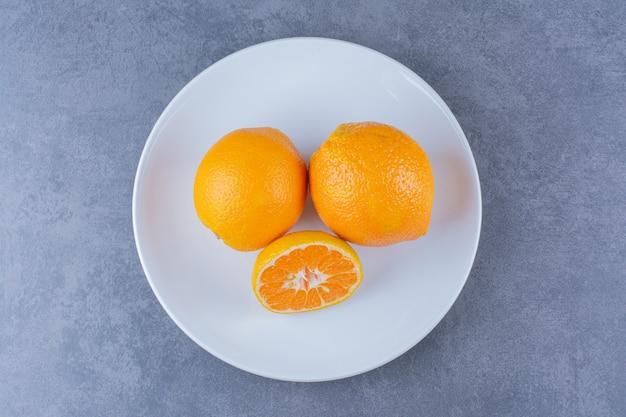 Сочные апельсины на тарелке, на темной поверхности