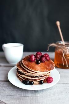Сочные блины с ягодами и медом на белой тарелке, ложке, банке, деревянном столе, кофейной чашке. фото высокого качества
