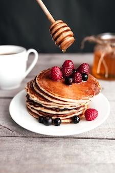 Сочные блины с ягодами и медом на белой тарелке, ложке, банке, деревянном столе, кофейной чашке.