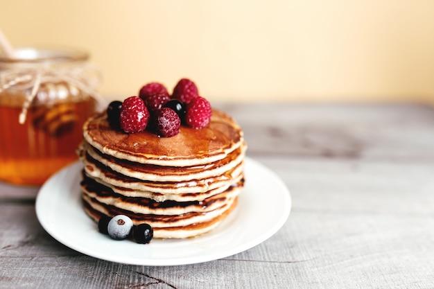 Сочные блины с ягодами и медом на белой тарелке, ложке, банке, деревянном столе. фото высокого качества