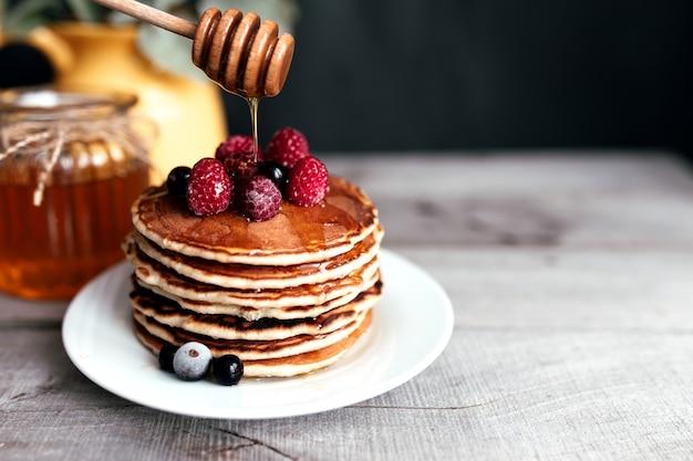 Сочные блины с ягодами и медом на белой тарелке, ложке, банке, деревянном столе, желтой вазе с эвкалиптом. фото высокого качества