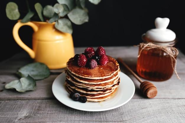 Сочные блины с ягодами и медом на белой тарелке, ложке, банке, деревянном столе, желтой вазе с эвкалиптом